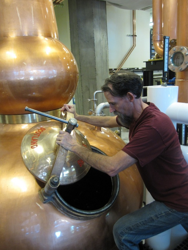 Micah opening the spirit still. Photo courtesy of Copperwork Distilling.